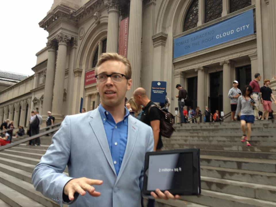 Man wearing blue blazer and holding iPad standing outside of the Metropolitan Museum of Art