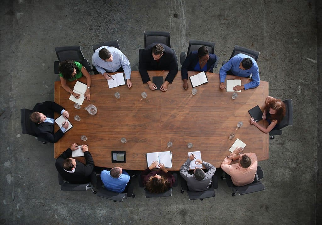 overhead view of CEO meeting sitting around a desk