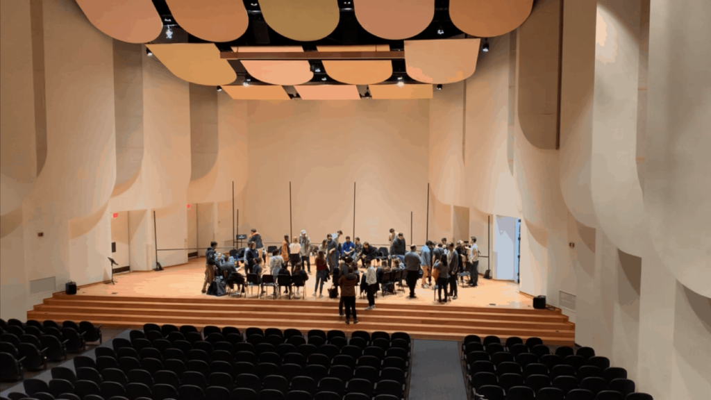 Large recital hall on the campus of Wake Forest University. Black chairs and people on stage