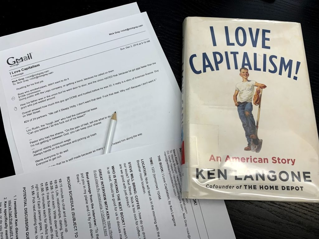Two sheets of paper plus a library copy of the book I Love Capitalism by Ken Langone