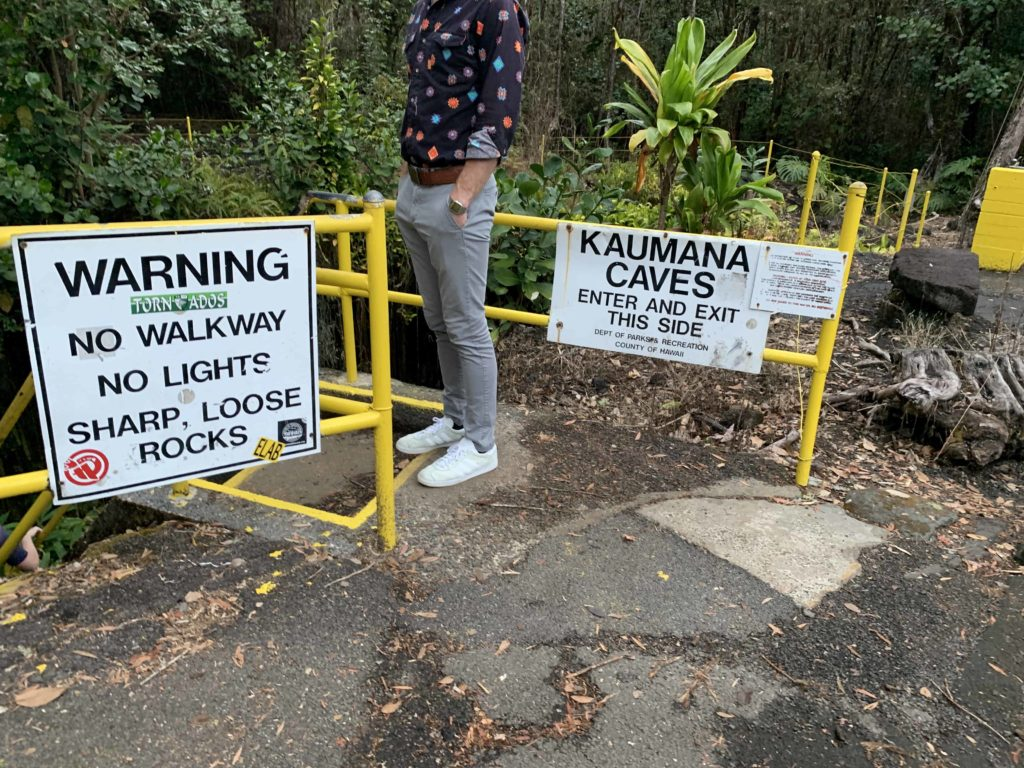Lower half of a man wearing pants and a shirt, and signs that way WARNING and KAUMANA CAVES