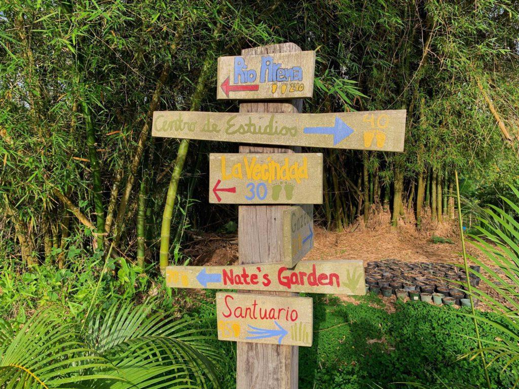 Wooden sign with locations pointing to Rio Arena, Centro de Estudio, La Vecindad, Nate's Garden, and more
