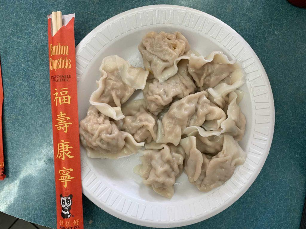White styrofoam plate, chopsticks on left, and 10 dumplings on plate from Shu Jiao Fu Zhou