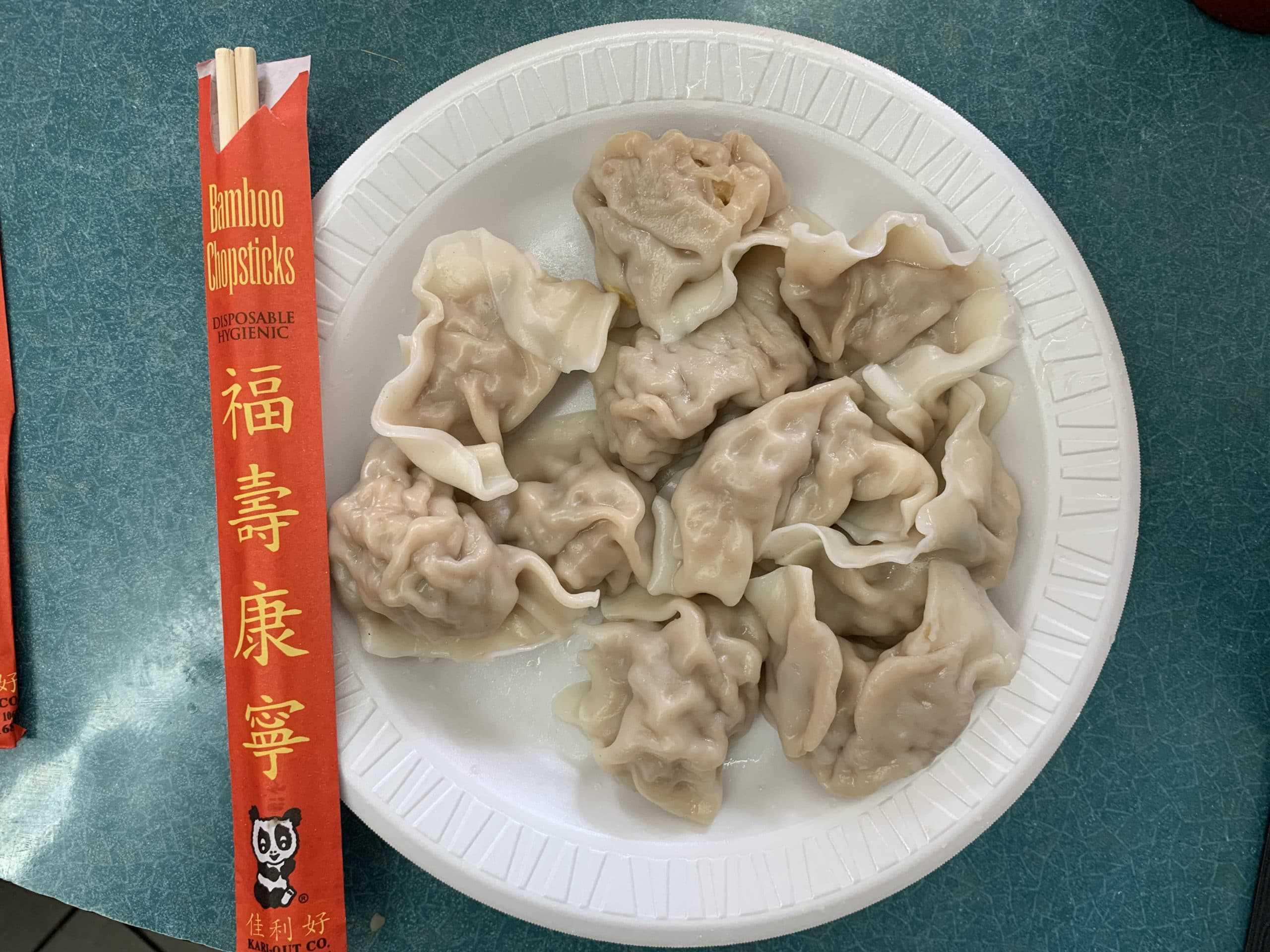 White styrofoam plate, chopsticks on left, and 10 dumplings on plate