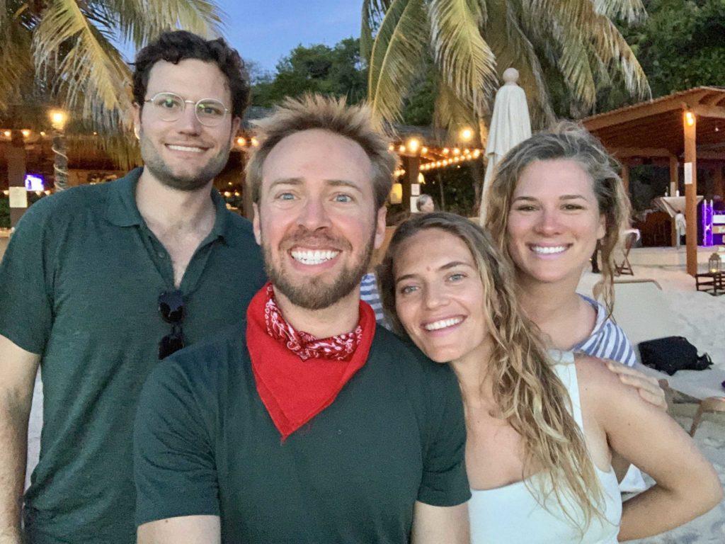 Four people in selfie mode on the beach in Roatan