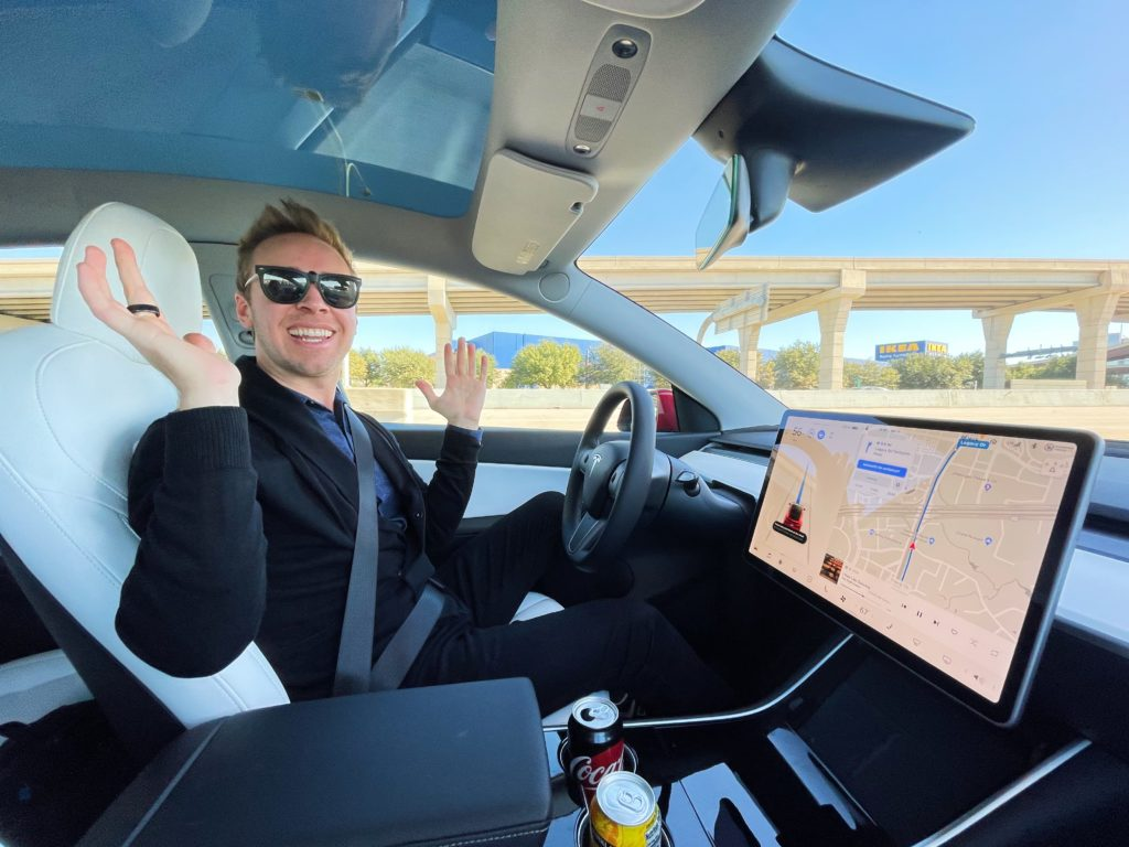 man sitting in driver's seat of Tesla Model Y car, looking at camera and smiling (Nick Gray)