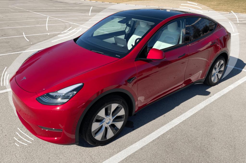 Exterior shot of a red color Tesla Model Y car in a parking lot