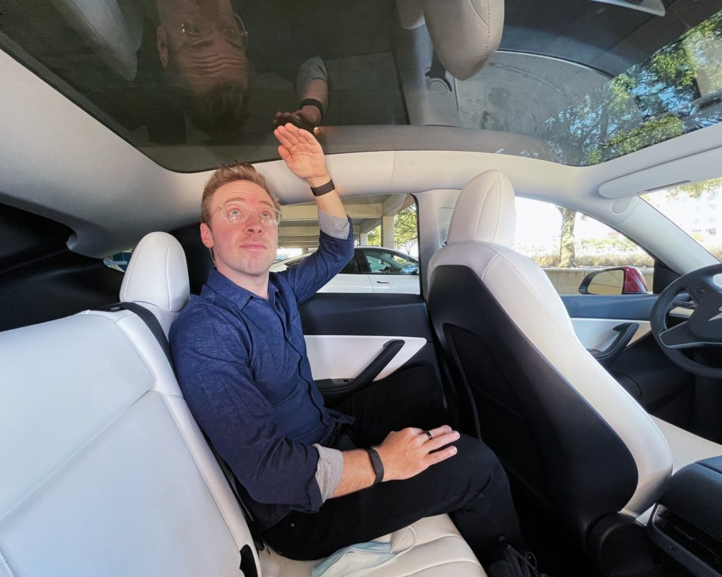 man sitting in the backseat of a Tesla Model Y with white interior, hand is raised to show the height above head