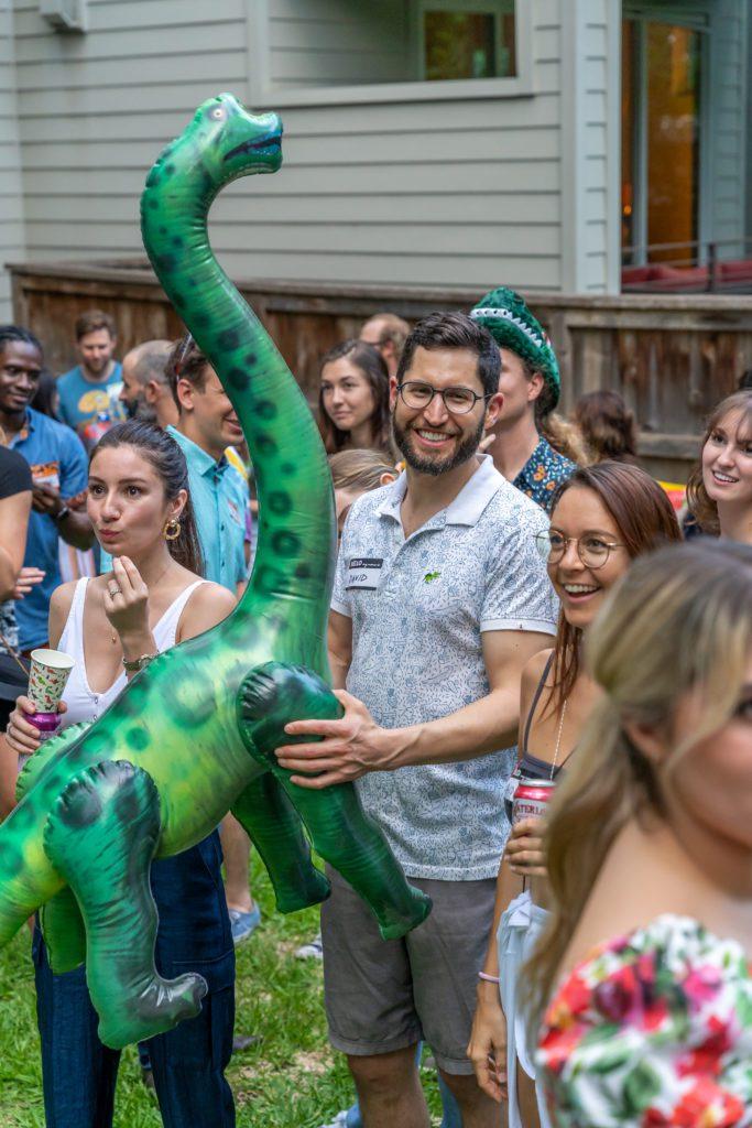 A man named David Shapiro holding an inflatable brontosaurus dinosaur
